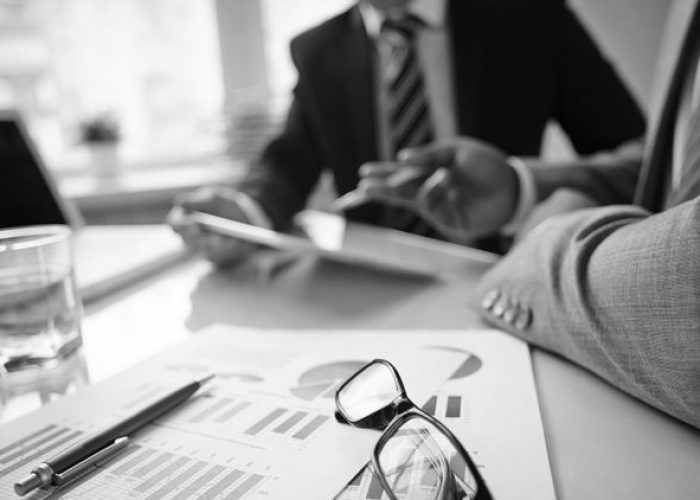Image of eyeglasses and financial documents at workplace with businessmen discussing ideas near by